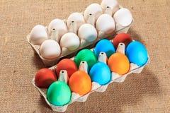 Huevos de Pascua blancos y coloreados en harpillera imagenes de archivo