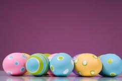 Huevos de Pascua brillantemente coloreados en fondo rosado Imagen de archivo