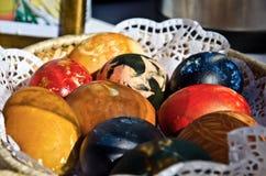Huevos de Pascua brillantemente coloreados en una cesta Fotografía de archivo libre de regalías