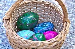 Huevos de Pascua brillantemente coloreados en una cesta Fotografía de archivo