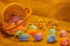 Huevos de Pascua, cesta y flores dispersados del albaricoque en fondo de la harpillera Imagenes de archivo