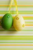 Huevos de Pascua colgados verdes y amarillos en fondo rayado Foto de archivo libre de regalías