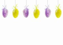Huevos de Pascua colgantes púrpuras y amarillos, aislados Imágenes de archivo libres de regalías