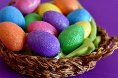 Huevos de Pascua coloreados chispeantes del caramelo que brillan en una cesta de mimbre imágenes de archivo libres de regalías