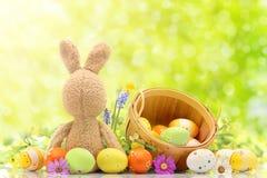 Huevos de Pascua coloreados con el conejo de conejito y la cesta en el medio del fondo verde Espacio libre para el texto foto de archivo libre de regalías