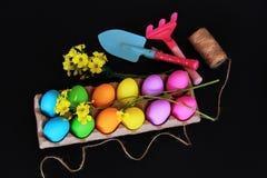 Huevos de Pascua coloreados con las herramientas que cultivan un huerto, niños flores amarillas de la pala que cultivan un huerto Imágenes de archivo libres de regalías