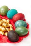 Huevos de Pascua coloreados en cesta con los huevos de Pascua de oro del chocolate Fotos de archivo libres de regalías