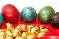 Huevos de Pascua coloreados en cesta con los huevos de Pascua de oro del chocolate Fotografía de archivo