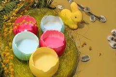 Huevos de Pascua coloreados en colores pastel y conejito amarillo foto de archivo