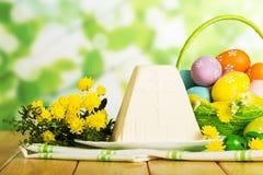 Huevos de Pascua coloreados en la cesta, postre tradicional del queso, flowe fotos de archivo