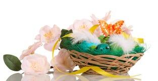 Huevos de Pascua coloreados en la ISO de la cesta, de las flores, de la cinta y de la mariposa fotografía de archivo libre de regalías