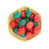Huevos de Pascua coloreados en la placa de la paja aislada en whi Foto de archivo