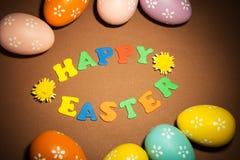 Huevos de Pascua coloreados, inscripción feliz de Pascua y flores en bro imagen de archivo