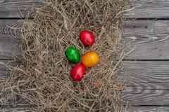 4 huevos de Pascua coloreados ponen en el heno seco en el tablero envejecido de madera fotos de archivo libres de regalías