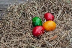 4 huevos de Pascua coloreados ponen en el heno seco en el tablero envejecido de madera fotos de archivo