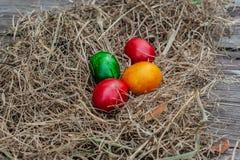 4 huevos de Pascua coloreados ponen en el heno seco en el tablero envejecido de madera imagen de archivo