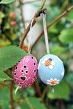 Huevos de Pascua coloreados que cuelgan en cintas en rama Imagen de archivo
