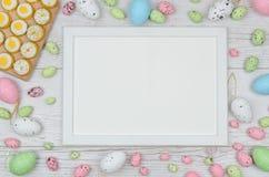 Huevos de Pascua coloreados sobre fondo de madera con el marco y espacio para la copia, texto, palabras Imagen de archivo