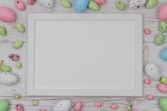 Huevos de Pascua coloreados sobre fondo de madera con el marco y espacio para la copia, texto, palabras Foto de archivo