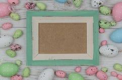 Huevos de Pascua coloreados sobre fondo de madera con el marco y espacio para la copia, texto, palabras Imagen de archivo libre de regalías