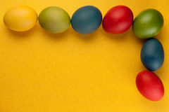 Huevos de Pascua coloridos adornados en fondo del color Fotos de archivo libres de regalías