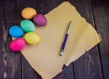 Huevos de Pascua coloridos con el documento en blanco y la pluma viejos sobre la madera rústica Imagen de archivo
