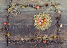 Huevos de Pascua coloridos con el gatito-sauce adornado en fondo de madera Foto de archivo