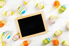 Huevos de Pascua coloridos con la pizarra foto de archivo