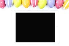 Huevos de Pascua coloridos con la tableta Imágenes de archivo libres de regalías