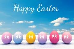 Huevos de Pascua coloridos con las caras en un tablero de madera con las letras felices de pascua Imagen de archivo libre de regalías