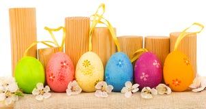 Huevos de Pascua coloridos con las flores blancas de la primavera y los registros de madera Imagen de archivo
