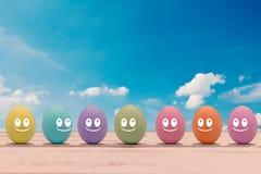 Huevos de Pascua coloridos con una cara en un tablero de madera Imagenes de archivo