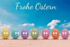 Huevos de Pascua coloridos con una cara en un tablero de madera con las letras Pascua feliz Fotografía de archivo