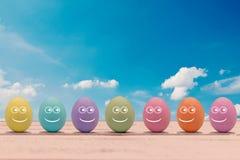 Huevos de Pascua coloridos con una cara en un tablero de madera con las letras Pascua feliz Imagenes de archivo
