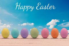 Huevos de Pascua coloridos con una cara en un tablero de madera con las letras Pascua feliz Foto de archivo