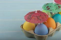 Huevos de Pascua coloridos debajo de los paraguas en un cartón foto de archivo