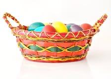 Huevos de Pascua coloridos en cesta fotos de archivo