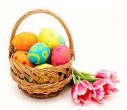Huevos de Pascua coloridos en cesta y flores aisladas en un blanco Fotos de archivo