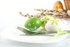 Huevos de Pascua coloridos en colores pastel con amentos y el carro Imagenes de archivo