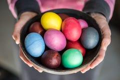 Huevos de Pascua coloridos en cuenco en las manos de la mujer foto de archivo libre de regalías