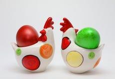 Huevos de Pascua coloridos en dos gallinas del juguete en el fondo blanco, imagen de la primavera Concepto de Pascua imagen de archivo