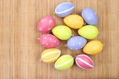 Huevos de Pascua coloridos en el fondo de bambú Imagen de archivo