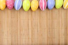 Huevos de Pascua coloridos en el fondo de bambú Fotografía de archivo