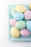 Huevos de Pascua coloridos en el fondo de madera blanco fotografía de archivo