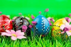Huevos de Pascua coloridos en fila en hierba verde Imagen de archivo libre de regalías