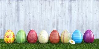 Huevos de Pascua coloridos en hierba con el fondo de madera blanco Imagenes de archivo