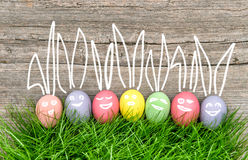 Huevos de Pascua coloridos en hierba verde Decoración divertida Imágenes de archivo libres de regalías