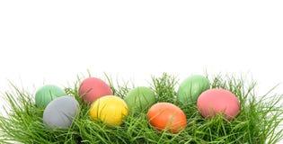 Huevos de Pascua coloridos en hierba verde sobre blanco Imagen de archivo libre de regalías