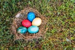 Huevos de Pascua coloridos en jerarquía en hierba verde Imágenes de archivo libres de regalías