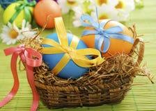 Huevos de Pascua coloridos en la cesta imagen de archivo